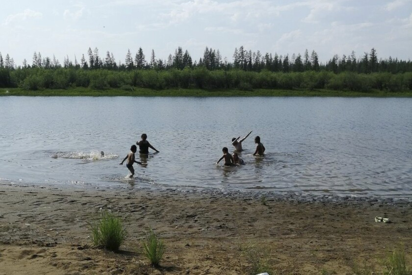 Children play in a lake near the Siberian town of Verkhoyansk, where the temperature reached 100.4 degrees Saturday.