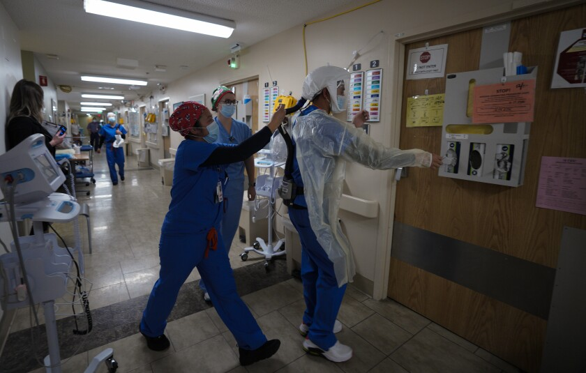 At Sharp Grossmont Hospital on Thursday, Dec. 17 nurses in the COVID unit respond to an alarm sounding in a patient's room.