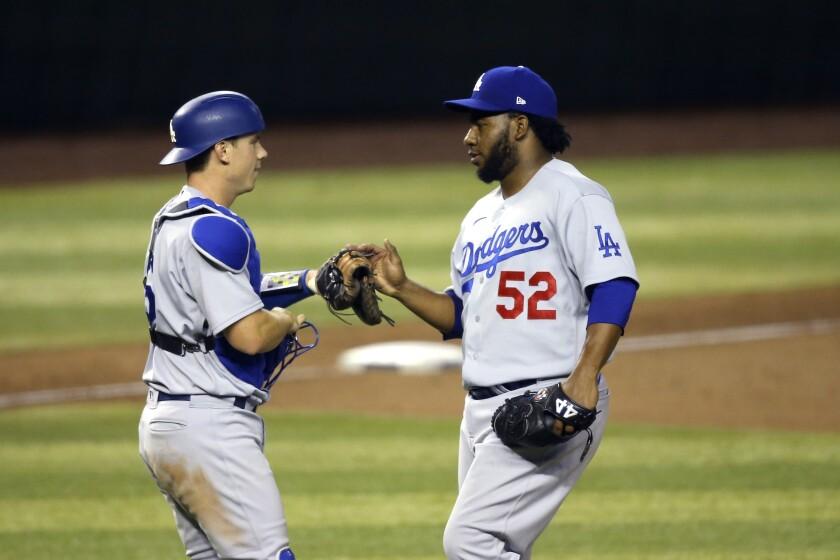 Dodgers relief pitcher Pedro Baez celebrates with catcher Will Smith.
