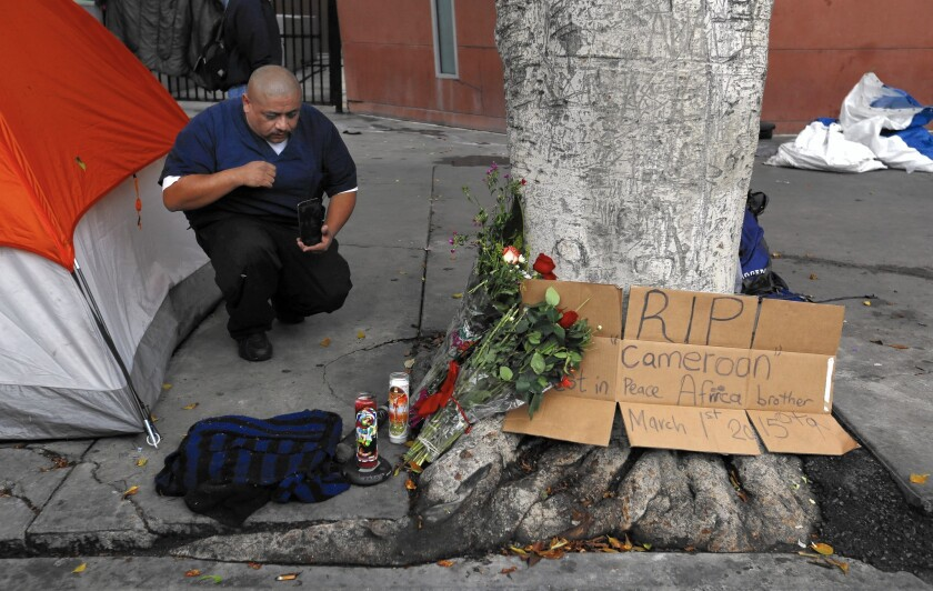 Fernando Avila kneels at the makeshift memorial near the site of Sunday's officer-involved shooting in downtown L.A.'s skid row.