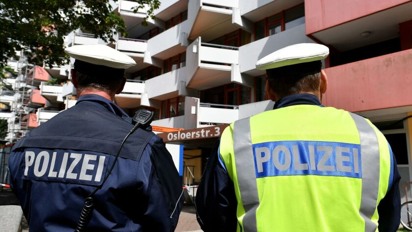 Police officers stand guard in front of an apartment block in the Chorweiler district of Cologne, Germany, on June 13. During a German special forces raid late on June 12, police found materials including ricin.