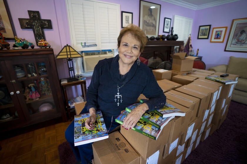 """Local author Maria Garcia sits on dozens of boxes containing her new book, """"We Made San Diego,"""""""