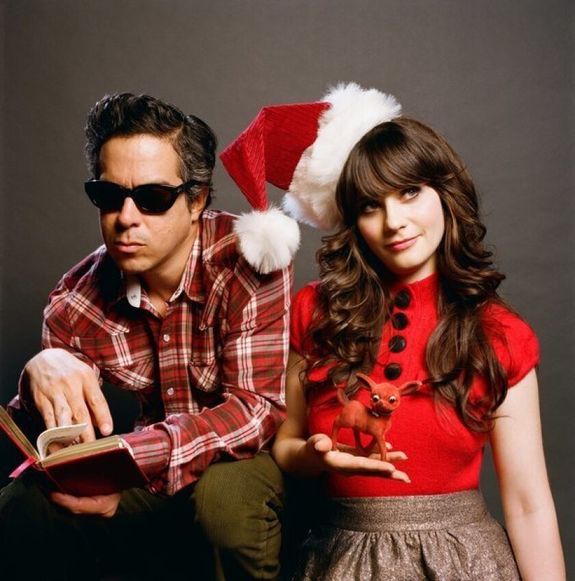 She & Him are M. Ward, in dark sunglasses and paging through a book, and Zooey Deschanel. wearing a Santa hat and holding a Rudolph figurine.