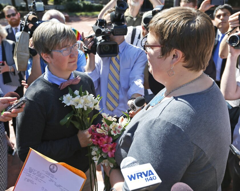 Nicole Pries, left, and Lindsey Oliver exchange vows Monday, Oct. 6, 2014, as the couple become one of the first same-sex couples in Virginia to be married, outside a Richmond Court building in Richmond, Va. The couple were the first in the Richmond are to be married after the US Supreme Court refused to overturn same-sex marriage prohibitions. (AP Photo/Steve Helber)