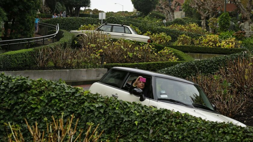 A woman takes a selfie while riding down the crooked section of Lombard Street in San Francisco. The street with eight hairpin turns draws about 2 million drivers a year.