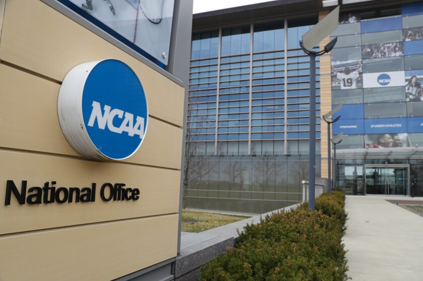 """FILE - This is a March 12, 2020, file photo showing NCAA headquarters in Indianapolis. The NCAA Board of Governors called for a special constitutional convention in November to initiated dramatic reform in the governance of college sports that could be in place as soon as January. The NCAA said it wants to """"reimagine"""" how to more effectively manage the needs of college athletes.(AP Photo/Michael Conroy, File)"""