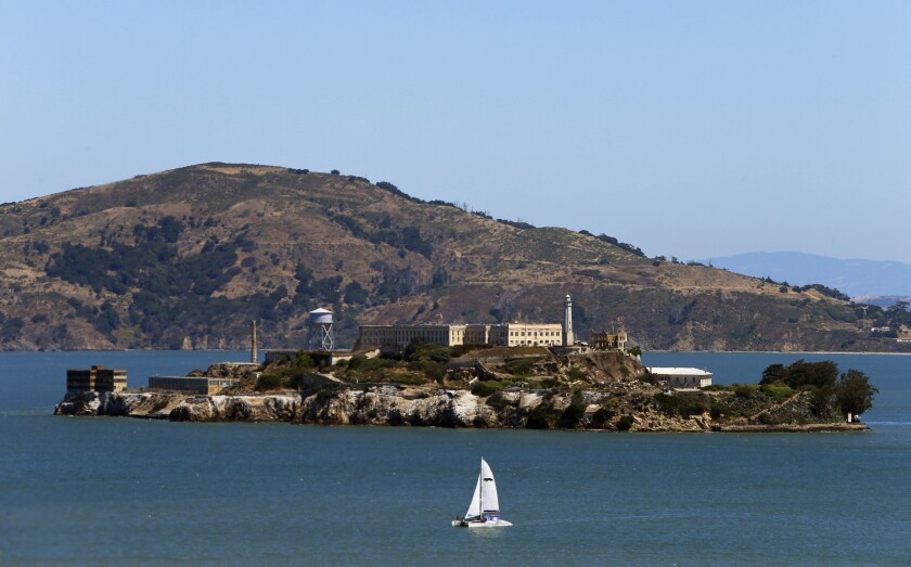A sailboat passes Alcatraz on a sunny day in San Francisco.
