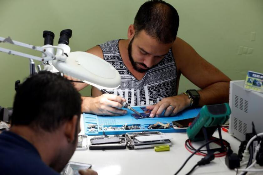 This young man owns a business repairing cell phones in Havana and is one of many examples of how Cuba has gone from a completely state-run economy to a gradual opening to foreign investment and the emerging private sector. EFE-EPA/File