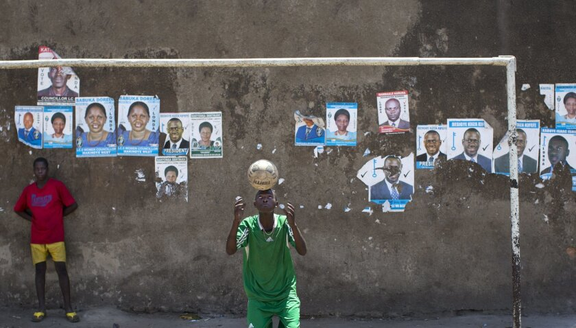 Boys play football and practice balancing tricks in front of a wall plastered with campaign posters for opposition leader Kizza Besigye, as well as for local members of Parliament, in a poor market area of the capital Kampala, Uganda Wednesday, Feb. 17, 2016. On the eve of presidential elections, a