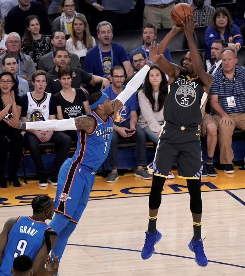 El jugador de los Warriors de Golden State Kevin Durant (d) lucha por el balón con Carmelo Anthony (i) de los Thunder de Oklahoma City durante su partido de la NBA. EFE