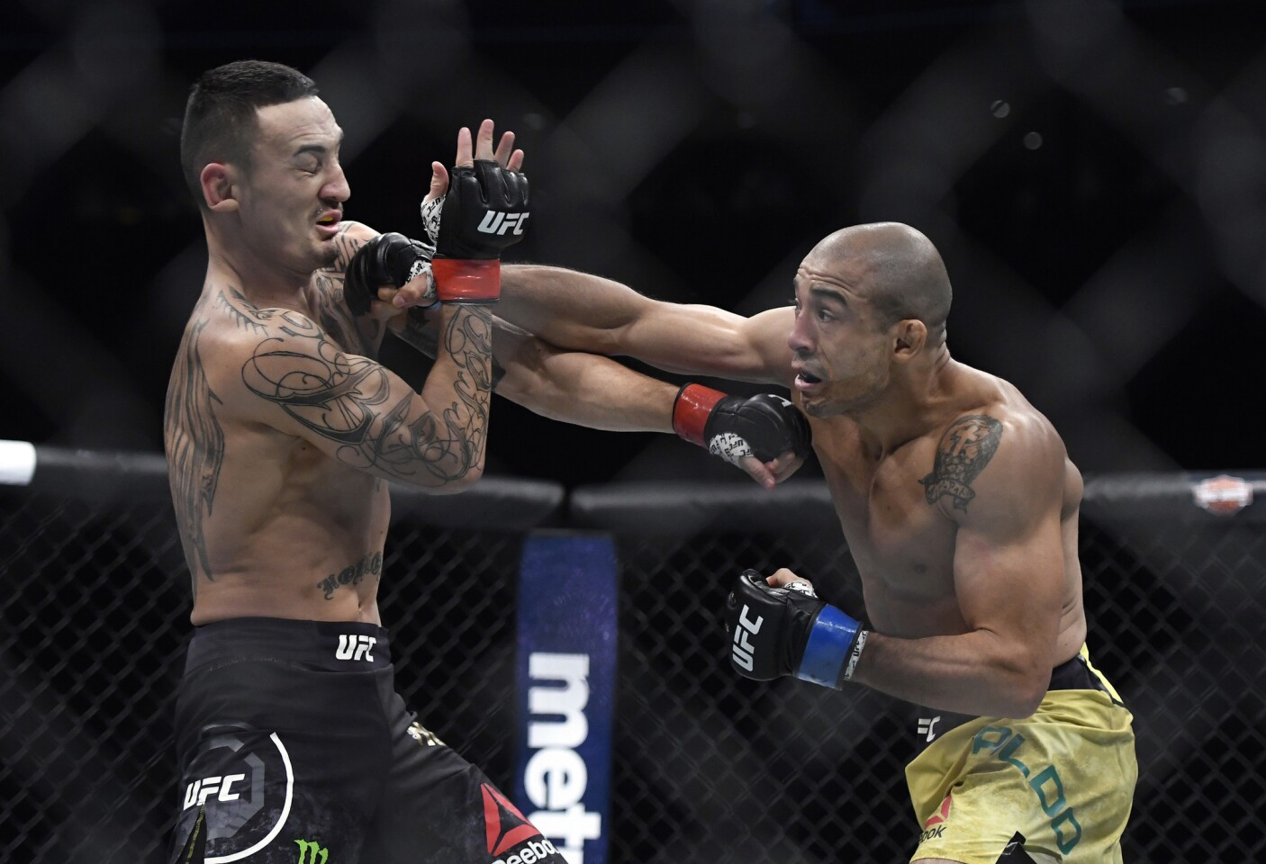 Jose Aldo lands an overhand right against Max Holloway during the first round of their featherweight title fight at UFC 218.
