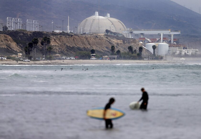 Surfers wade in front of the closed San Onofre nuclear power plant in north San Diego County.