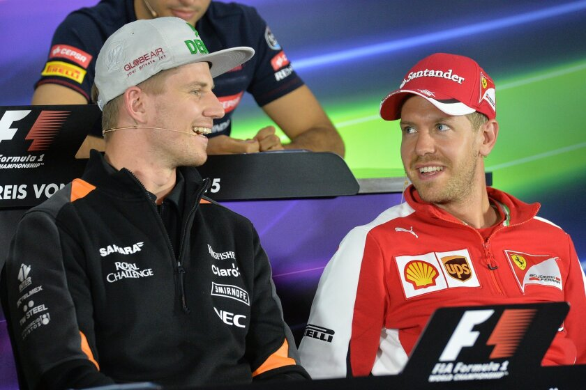 Force India driver Nico Huelkenberg of Germany and Ferrari driver Sebastian Vettel of Germany, right, smile during a press conference prior to the Formula One Grand Prix, at the Red Bull Ring in Spielberg, southern Austria, Thursday, June 18, 2015. (AP Photo/Kerstin Joensson)