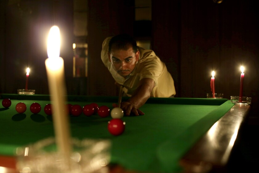 An Egyptian man plays snooker by candlelight Saturday at a club in Giza, Egypt.