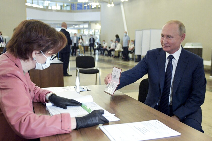 Russian President Vladimir Putin shows his passport as he arrives to vote at a Moscow polling station.