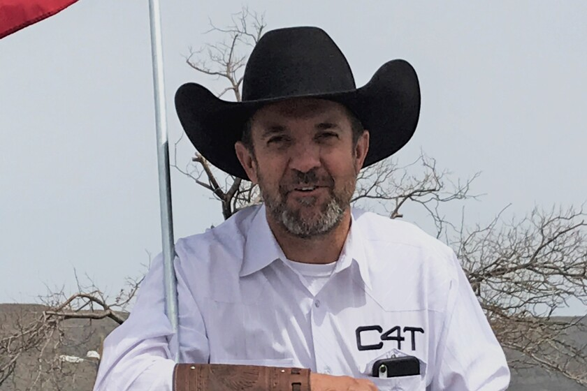 Couy Griffin in a black cowboy hat and a white shirt with 'C4T' above the breast pocket.