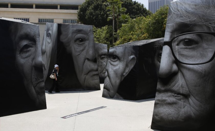 """A woman walks through a portion of """"iwitness,"""" the first public art installation in Grand Park , featuring large-scale photographic sculptures bearing portraits of Armenian Genocide survivors and their stories."""
