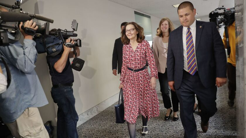 Gina Haspel, center, who is President Trump's nominee to lead the CIA, walks past TV cameras as she heads to a meeting on Capitol Hill on Monday.