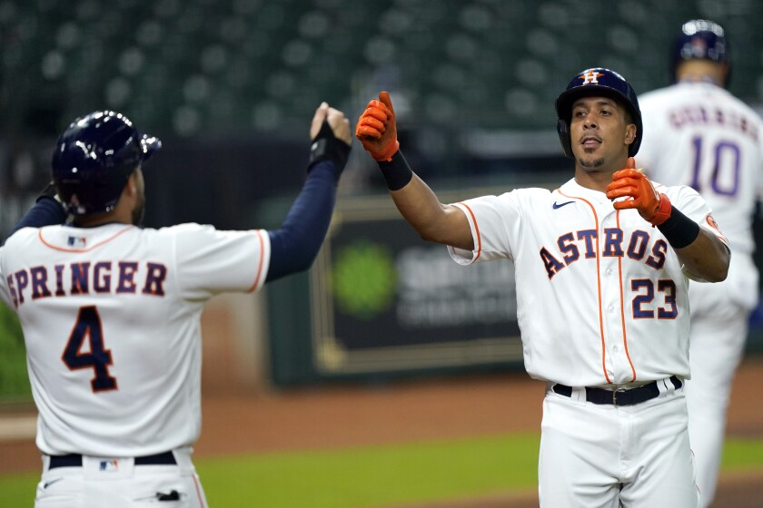 Houston Astros' Michael Brantley (23) celebrates with George Springer (4) after hitting a home run against the Texas Rangers during the first inning of a baseball game Wednesday, Sept. 2, 2020, in Houston. (AP Photo/David J. Phillip)