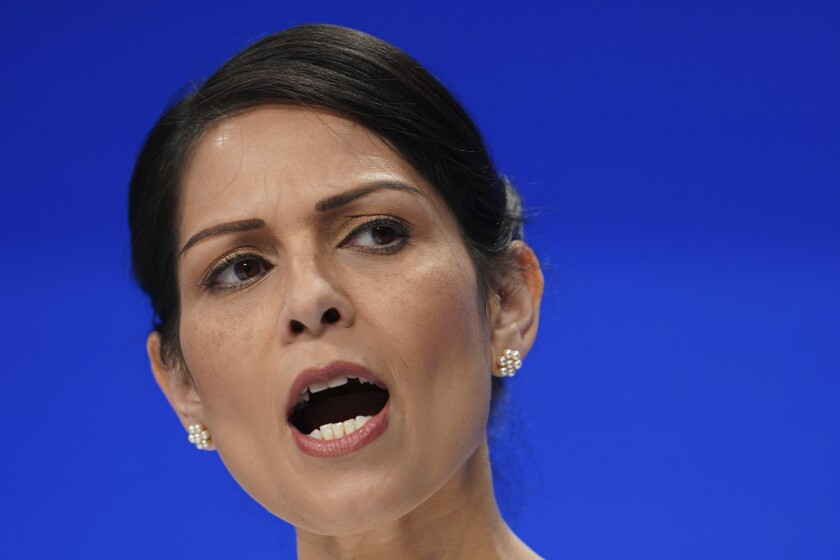 """FILE - In this Tuesday, Oct. 5, 2021 file photo, Britain's Home Secretary Priti Patel speaks at the Conservative Party Conference in Manchester, England. The chief executive of Britain's biggest phone company, BT, proposed the """"walk me home"""" service in a letter to Home Secretary Priti Patel, saying it would complement the existing nationwide emergency number. Once a woman activated an app on her phone, the service would track her journey and send an alert to her emergency contacts if she didn't reach her destination on time, Philip Jansen said in the letter. (AP Photo/Jon Super, File)"""