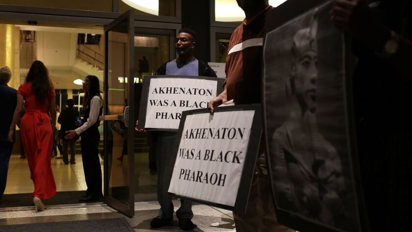 "Kamal Mohsin holds a protest sign with other demonstrators outside Dorothy Chandler Pavilion on Saturday night. The protest was over the casting of a white singer in the title role of Los Angeles Opera's new production, ""Akhnaten,"" about an Egyptian pharaoh."
