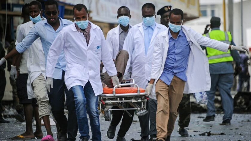 Paramedics carry a body away from the scene of Saturday's attack in Mogadishu.