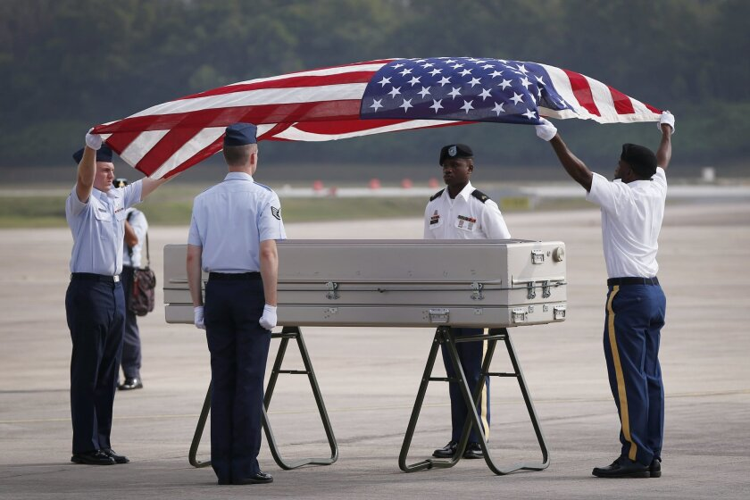 A U.S. military honor guard prepares to put U.S. national flag after they accepted the human remains in a military ceremony that were recovered from a 1945 crash of a U.S. military transport plane, in Kuala Lumpur, Malaysia, Thursday, Nov. 5, 2015 After the military ceremony attended by U.S. Defens