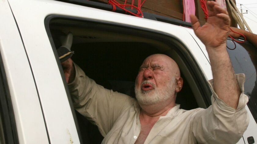 An Iraqi old man reacts inside a mini bus during a funeral of a victim after an early morning U.S. a
