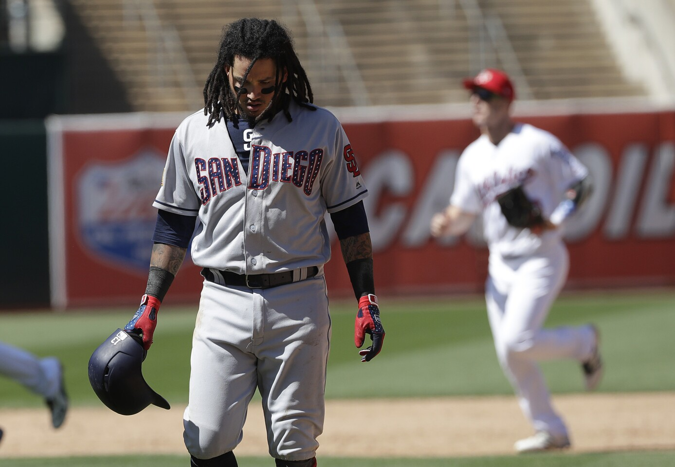 San Diego Padres' Freddy Galvis walks off the field after the team's baseball game against the Oakland Athletics in Oakland, Calif., Wednesday, July 4, 2018. The Athletics won 4-2. (AP Photo/Jeff Chiu)