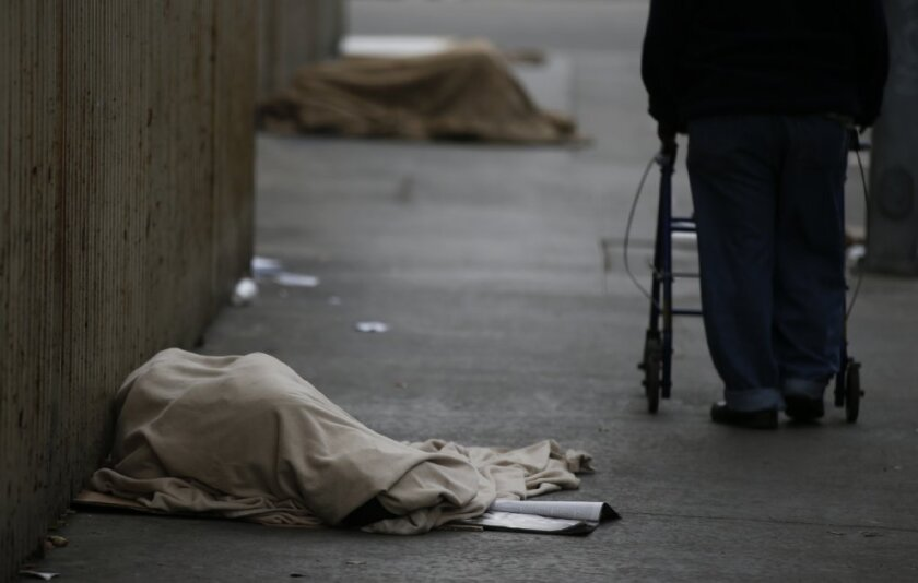 Homeless men and women draped in blankets sleep on the sidewalk along Wall Street in downtown Los Angeles in January.
