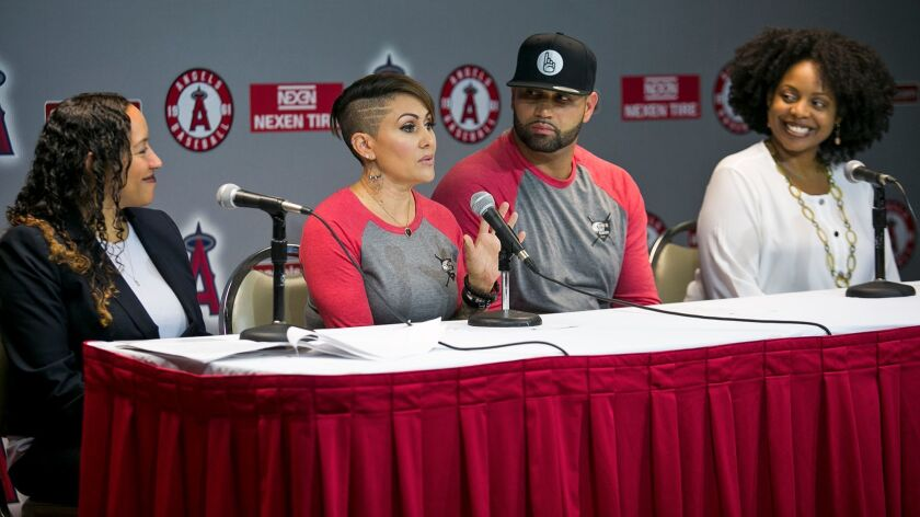 "Deidre Pujols speaks as husband Albert looks on during a news conference about ""Strike Out Slavery"""