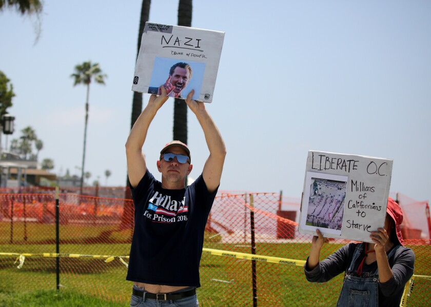 A handful of protesters hold up signs next to the fenced-off Main Beach Park in Laguna Beach