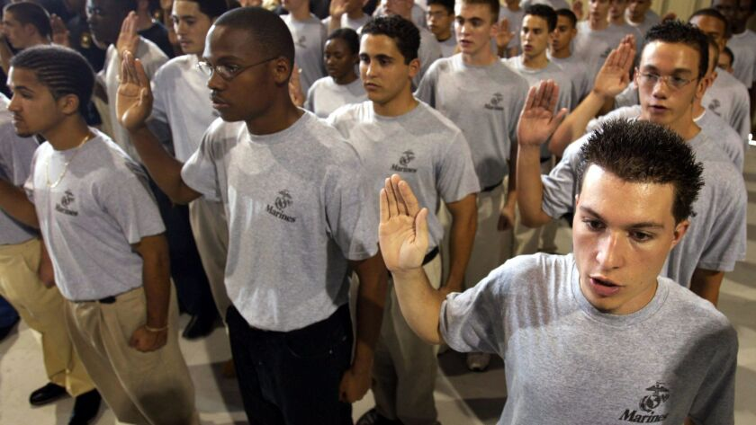 Recruits raise their hands during a joint forces swearing-in ceremony for enlistees April 29, 2004, in Fort Lauderdale, Florida.