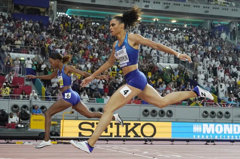 FILE - Dalilah Muhammad, left, of the United States, finishes ahead of Sydney Mclaughlin, right, also from the United States, to win the the women's 400 meter hurdles final and set a new world record at the World Athletics Championships in Doha, Qatar, in this Friday, Oct. 4, 2019, file photo. The most anticipated race of the U.S. track and field trials may be the women's 400 hurdles, where world record holder Dalilah Muhammad tries to hold off the up-and-comer Sydney McLaughlin. (AP Photo/David J. Phillip, File)
