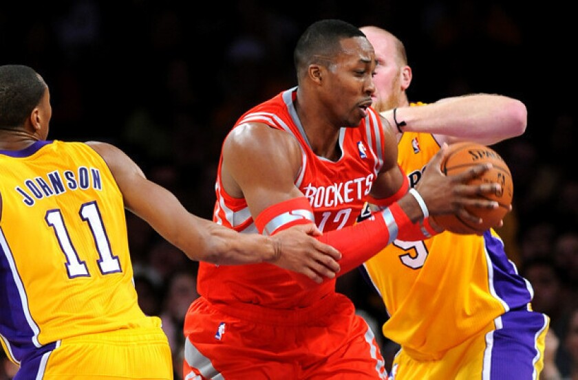 Rockets center Dwight Howard splits the double-team defense of Lakers forward Wesley Johnson and center Chris Kaman on a drive to the basket in the first half Wednesday night at Staples Center.