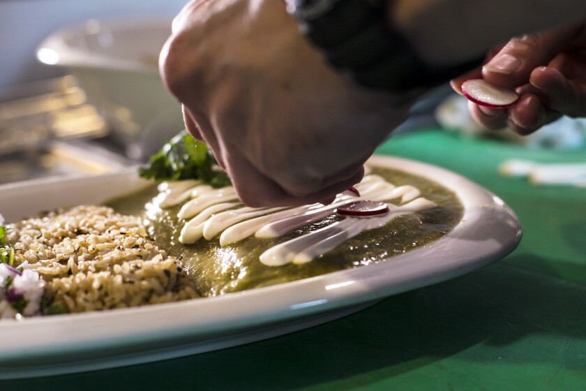 Christian Morales prepares a chicken enchilada with salsa verde