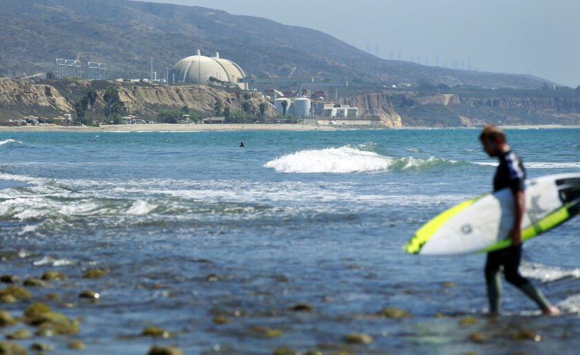 A surfer walks in as the San Onofre nuclear power plant sits in the background.