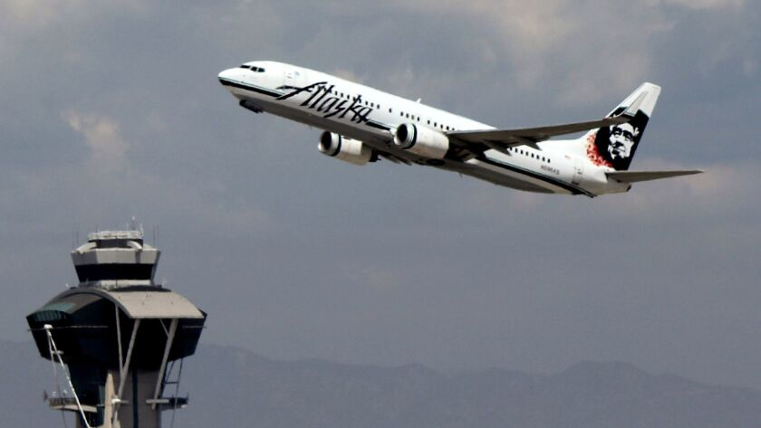 This Sept. 7, 2014 photo shows an Alaska Airlines plane taking off past the flight control tower fro