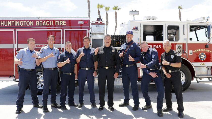 Huntington Beach Fire Chief Dave Segura, center, jokes around with members of team as they take a gr