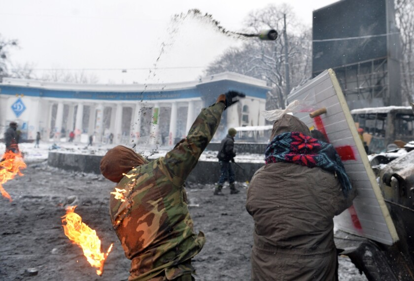 A protester throws a Molotov cocktail at police during clashes in the center of Kiev.