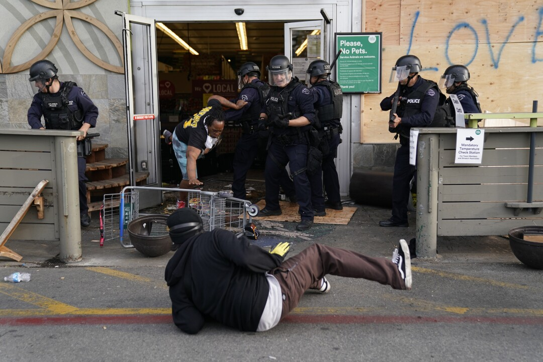 Protesters are thrown out of a Whole Foods Market in L.A.'s Fairfax District on Saturday.