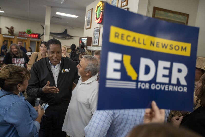 Remember candidate Larry Elder, second from left, talking to supporters during a stop at Philip de Original Daily on Monday.
