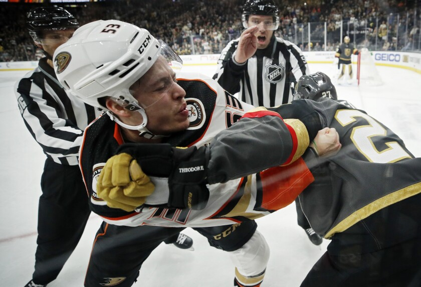Ducks left wing Max Comtois (53) fights with Vegas Golden Knights defenseman Shea Theodore (27) during the third period of a game Dec. 31.