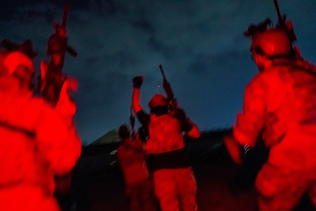 Soldiers seen from behind, lit in red light