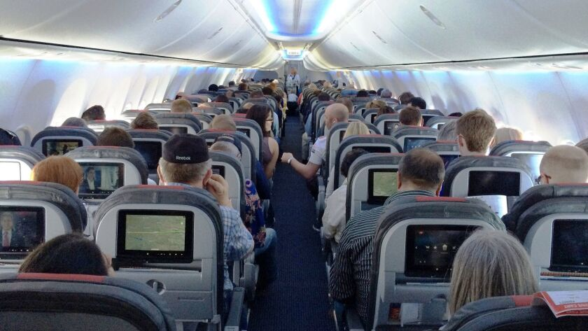 Passengers on an American Airlines 737 jet. The Federal Aviation Administration is required under a new bill to set minimum seat dimensions on airlines.