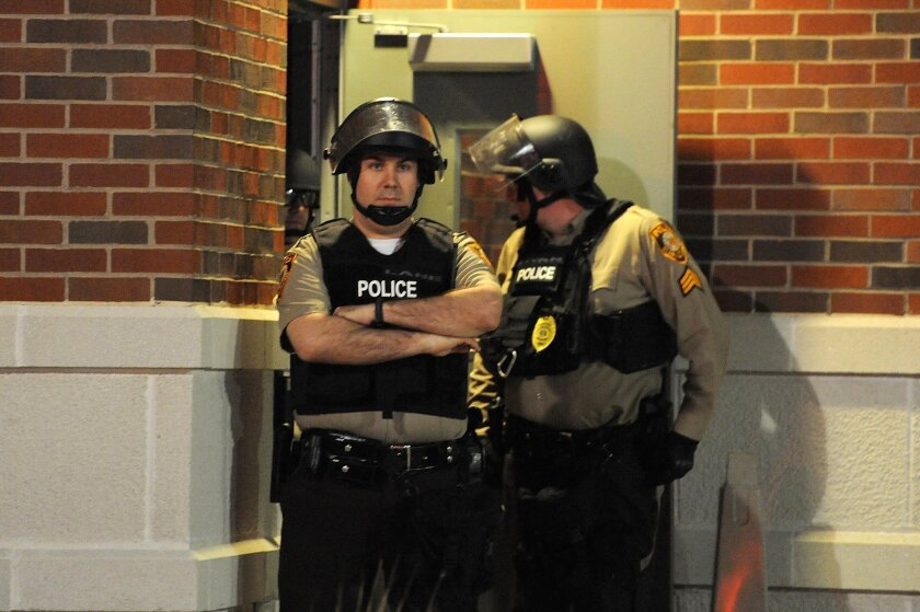 St. Louis County police officers stand in riot gear as protesters demonstrate outside the Ferguson Police Department in Ferguson, Mo., on Thursday. Two police officers were shot earlier that day.