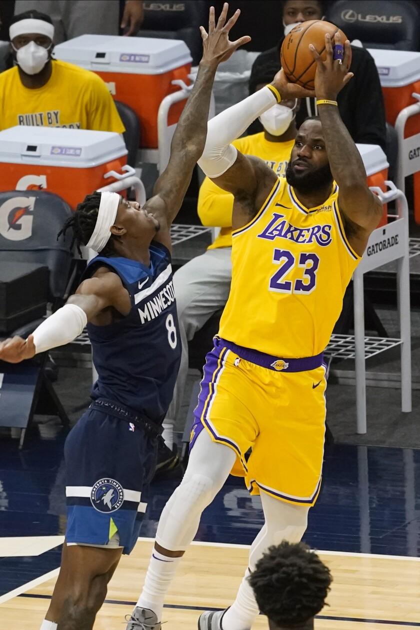 El alero de los Lakers de Los Ángeles LeBron James lanza el balón sobre Jarred Vanderbilt