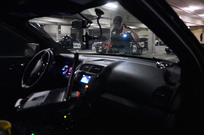 Chula Vista police officer Christopher Lawrence inspects his patrol car as he readies his car before roll call and the start of his shift in April 2018.