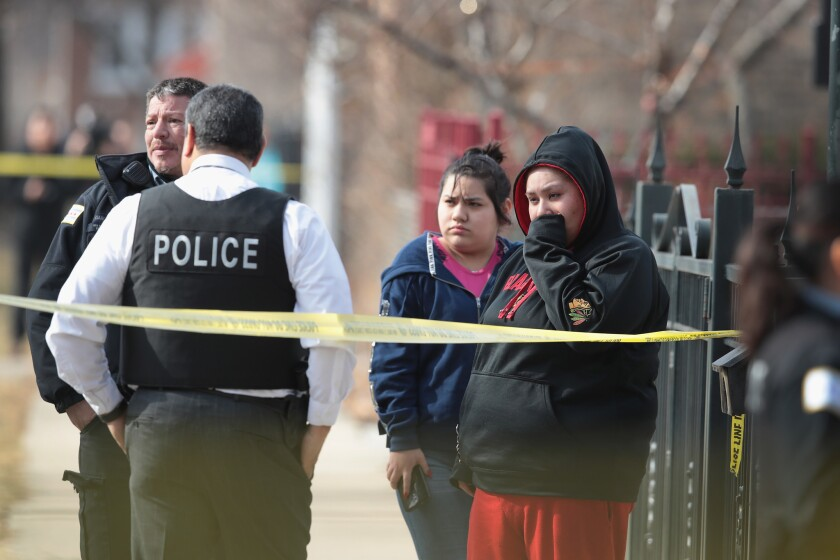 Police investigate the scene Feb. 6 after two people were discovered shot to death inside a Chicago apartment.