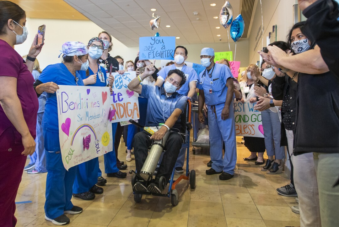 Armando Mendoza, 53, of Anaheim, celebrates with all his health-care professionals and his family after spending 45 days at St. Joseph Hospital in Orange. Mendoza was the hospital's second-ever COVID-19 patient.